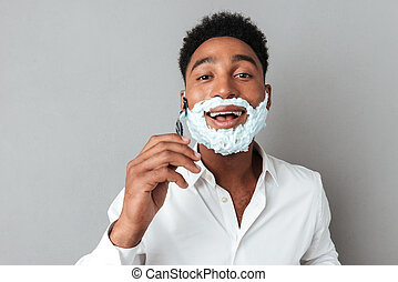 Young african man in shirt shaving with a razor