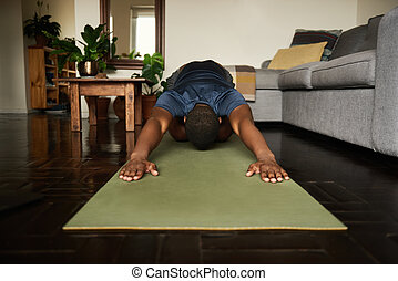 Young African man in the child's pose during yoga at home