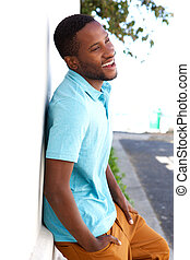 Young african man leaning against wall outside and smiling