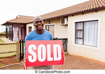 young african man outdoors with sold sign