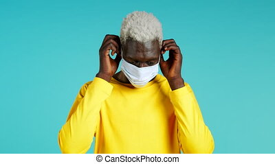 Young african man puts on face medical mask during coronavirus pandemic. Portrait on blue background. Protection with respirator against COVID-19 outbreak. High quality 4k footage