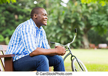 young african man sitting outdoors