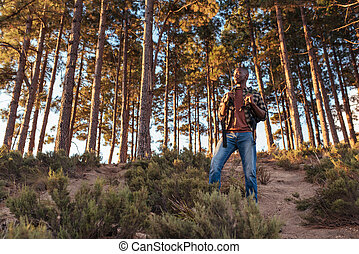 Young African man standing on a trail in the forest