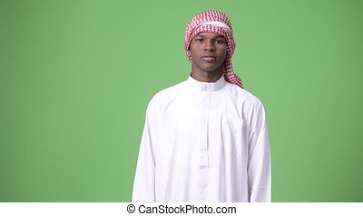 Young African man wearing traditional Muslim clothes against...