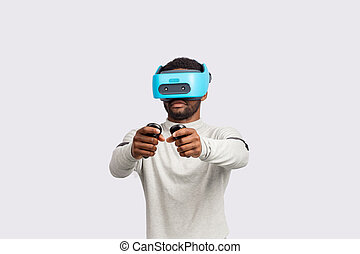 Young african man wearing virtual reality goggles isolated on white background