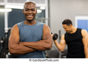 young african man with arms folded in gym