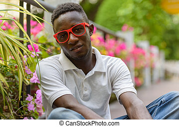 Young African man with eyeglasses sitting at the park outdoors
