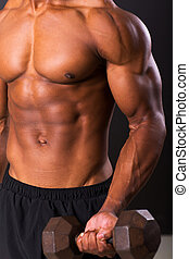 young african man working out with dumbbells on black...