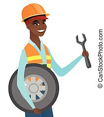 Young african mechanic with tyre and spanner.