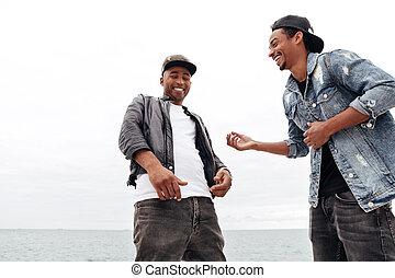 Young african men friends walking outdoors.