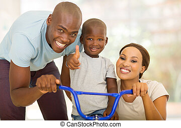 young african parents helping son to ride a bicycle