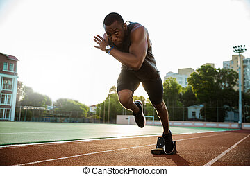 Young african runner running on racetrack