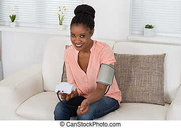 Woman Checking Blood Pressure - Young African Woman Checking...