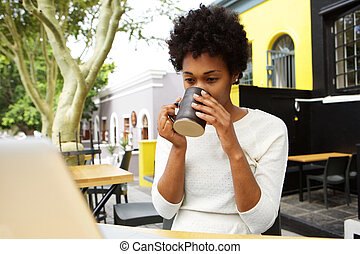 Young african woman drinking cup of tea
