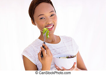 young african woman eating green salad at home