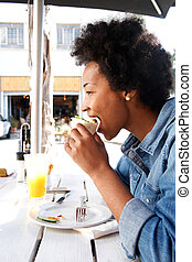 Young african woman eating sandwich at cafe