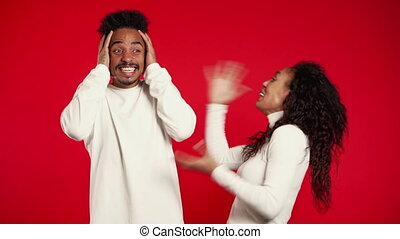 Young african woman emotionally screaming at her husband or boyfriend on red background in studio. Bored man covers ears with hands. Concept of conflict, problems in relationships.