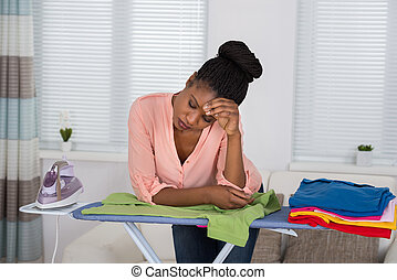 Woman Exhausted While Ironing Clothes