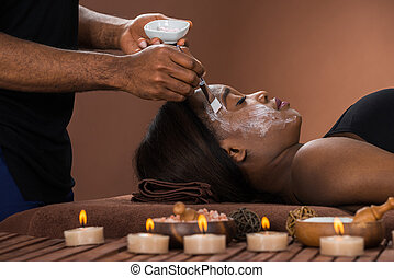 Woman Getting Facial Mask At Spa