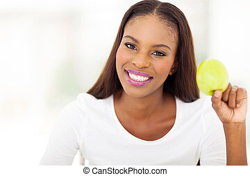 young african woman holding apple closeup