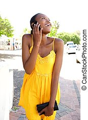 Young african woman in summer dress talking on cell phone
