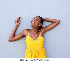 Young african woman in yellow dress a flower