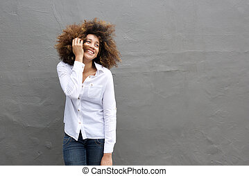 Young african woman laughing with hand in hair