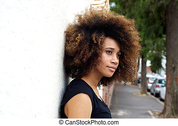 Young african woman leaning against wall