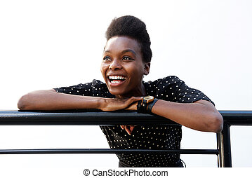 Young african woman leaning on railing and laughing