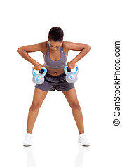 young african woman lift kettle bell weights with both hands...