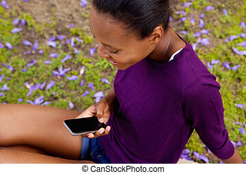 Young african woman looking at mobile phone