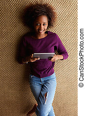Young african woman lying down with digital tablet