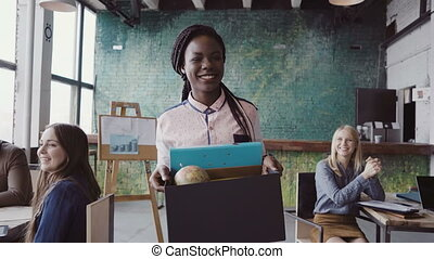 Young african woman recently hired for corporate job comes into her new office. Female holds box with personal belongings, walk through the coworking space, greets with new colleagues. Mixed race team