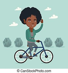 Young african woman riding bicycle in the park.