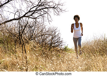 Young african woman running on mountain trail