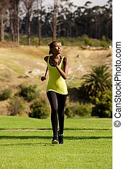 Young african woman running outdoors