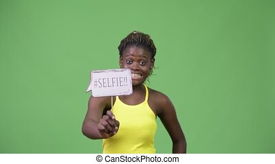 Young African woman showing selfie paper sign