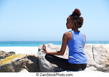 Young african woman sitting at beach in yoga pose