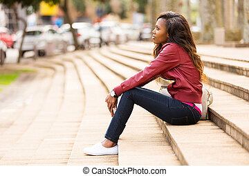 young african woman sitting outdoors - thoughtful young...
