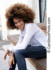 Young african woman sitting outside smiling