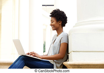 Young african woman sitting outside using laptop
