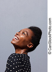 Young african woman smiling against gray background