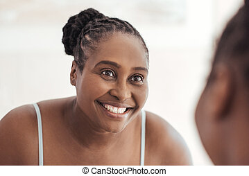 Young African woman smiling at her reflection in a mirror