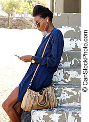 Young african woman standing outdoors using mobile phone
