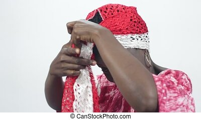 Young African woman ties her head with a scarf. - Young...