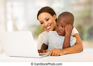 young african woman using laptop with her son