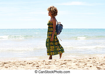 Young african woman walking on the beach
