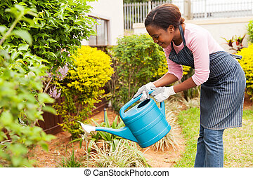 young african woman watering her garden - happy young...