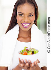 young african woman with bowl of salad