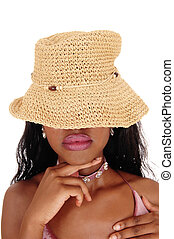 Young African woman with straw hat over eyes